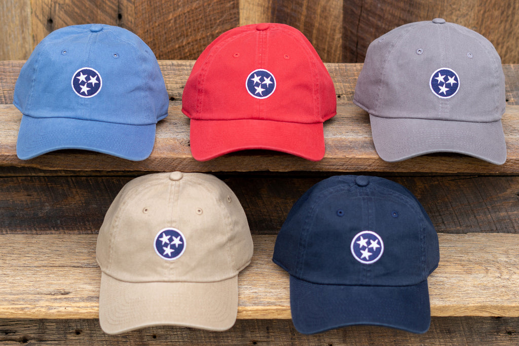 Volunteer Traditions Tennessee Tristar Hats. Stone Blue with Navy, Red with Navy, Old South Grey with Navy, Khaki with Navy, and Navy with Navy Tristar Hats on wood.