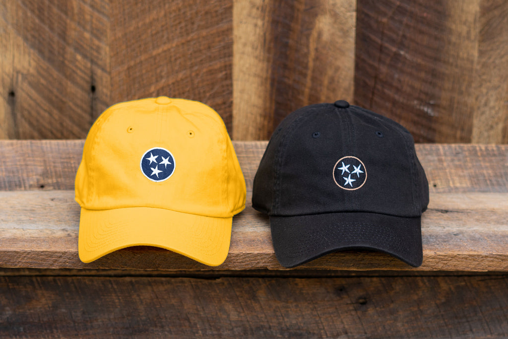 Volunteer Traditions Tennessee Tristar Hats. Gold with Navy and Black with Gold Tristar Hats on wood.