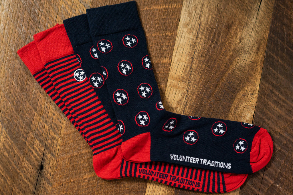 Volunteer Traditions Tristar Socks. Navy with Red Tristar and Navy with Red Stripe Sock Bundle on wood.