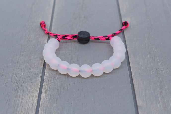 Translucent adjustable silicone bead bracelet on pink and black paracord