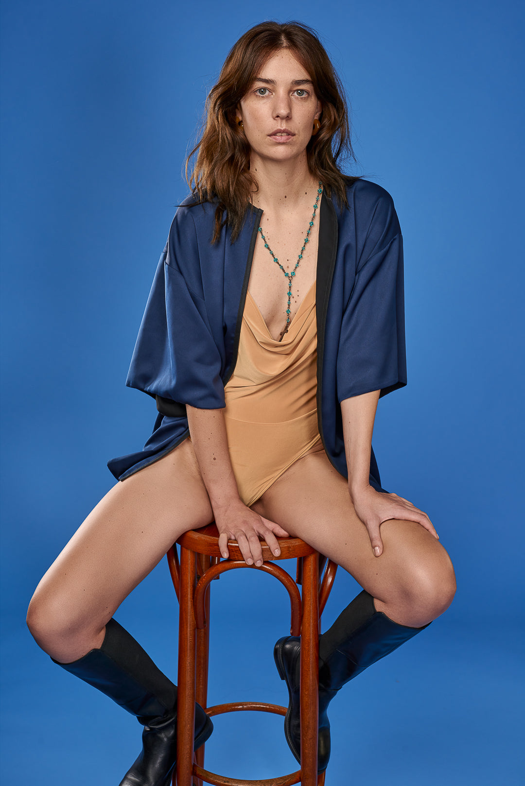 Lena Regh wearing blue kimono and yellow bodysuit with a blue backdrop