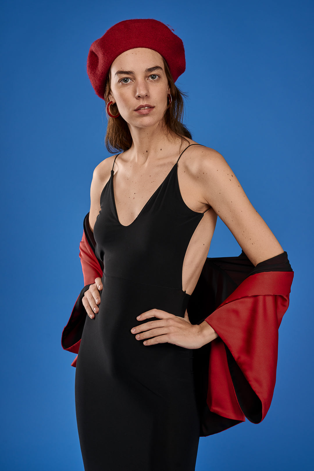 Lena Regh in a black dress with a red béret