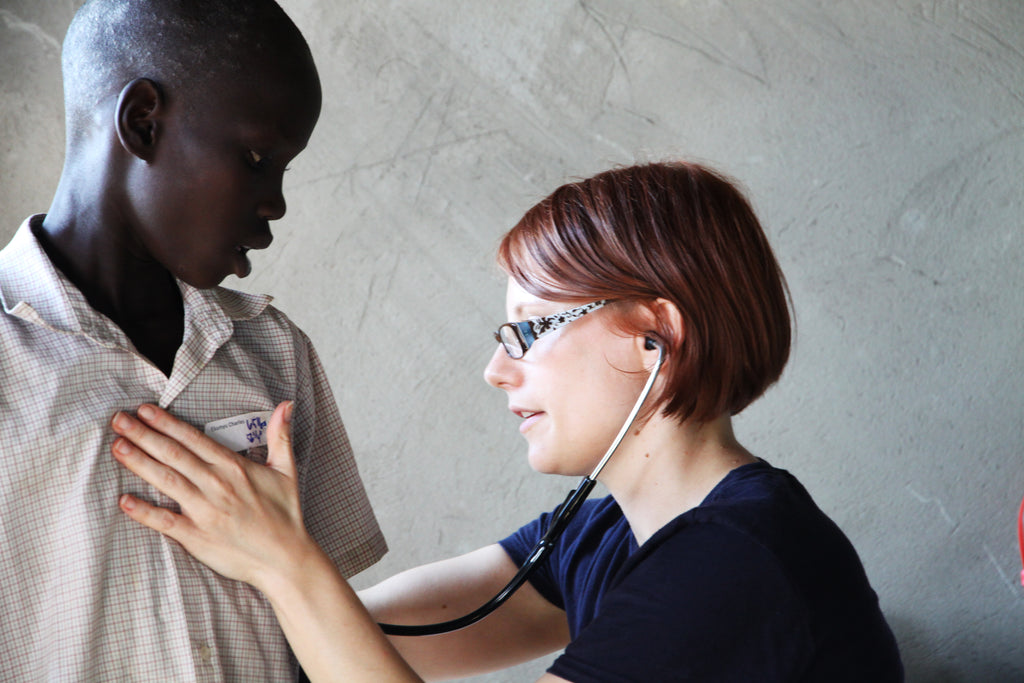 Doctor checking Ugandan boy heart rate