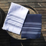small white and navy dina terry backed towels on wooden barrel