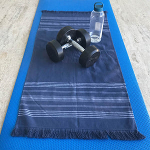 small navy dina terry backed towel open on gym mat