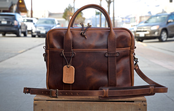 Light brown leather briefcase measuring 15.5 inches long, 11.75 inches tall and 4.5 inches wide.  Two light brown leather straps riveted to front leather pocket that turn into rolled handles.  Light brown leather shoulder strap with antique brass roller buckles attached to briefcase.