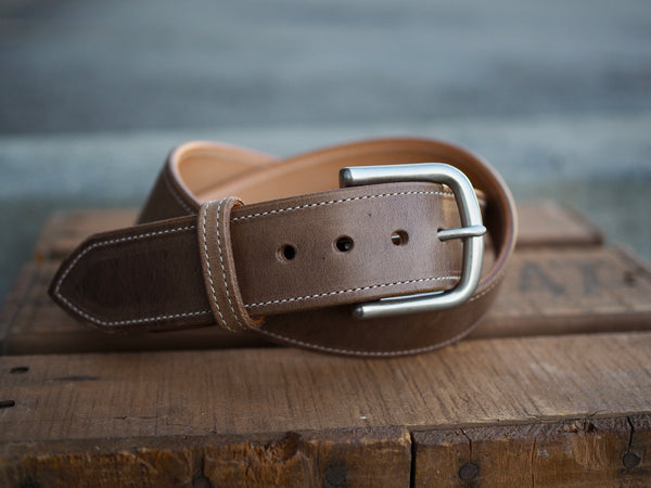 Light brown leather belt with white border stitch and rounded matte nickel buckle.
