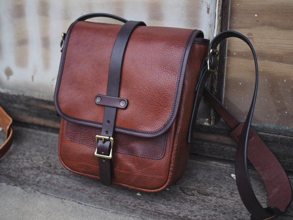 "Brown leather bag with flap measuring 9"" wide, 11"" tall, 3.5"" deep.  Dark brown leather strap with brass roller buckle securing flap in place."