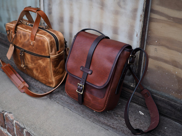 Light brown leather briefcase measuring 14 inches wide,  11 inches tall and 3.5 inches depth with light brown leather strap.  Brown leather bag with flap.  Dark brown leather binding and shoulder strap.  Dark brown strap with brass roller buckle secures flap down.
