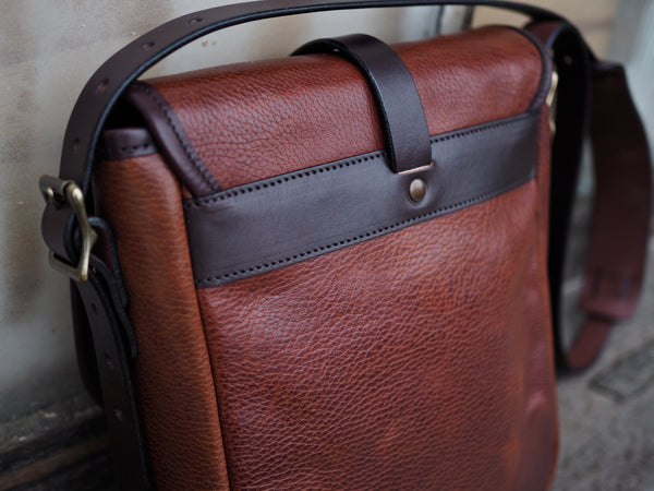 Back of brown leather bag with flap.  Dark leather binding.  Dark leather band attached to bag horizontally with copper rivet to flap.