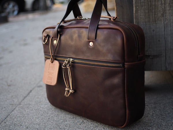 Dark brown leather briefcase measuring 14 inches wide, 11 inches tall and 3.5 inches deep. YKK Brass zipper on front panel of briefcase to make pocket. YKK Brass zipper at top of briefcase. Dark brown leather handles copper riveted to bag. Antique brass D-ring upper left corner of bag for shoulder strap to attach to.