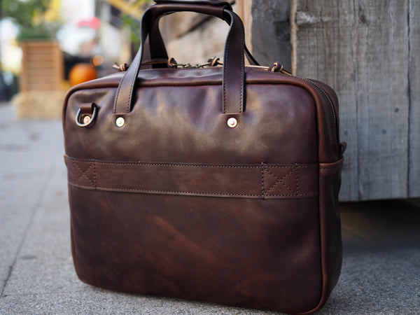 Back of Dark brown leather briefcase.  Dark brown leather handle copper riveted to bag.  Antique brass D-ring riveted to upper left corner of bag.