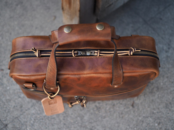 YKK brass zipper at top of leather briefcase. Medium brown leather handles with handle wrap that has antique brass snaps.
