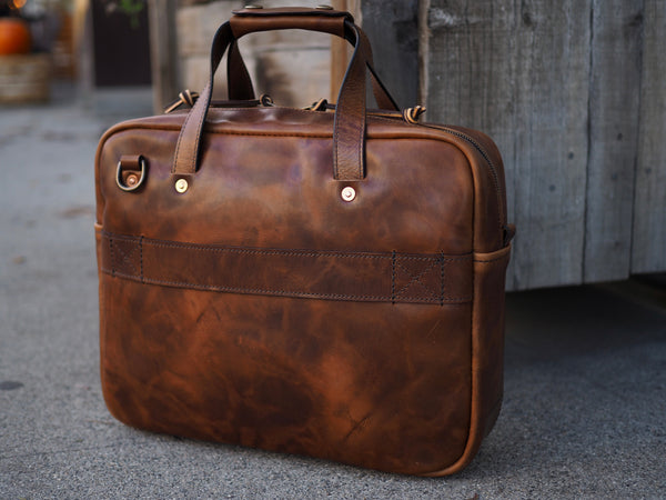 Back of medium brown leather briefcase. Medium brown leather handle copper riveted to bag. Antique brass D-ring riveted to upper left corner of bag.  Medium brown leather strap sewn horizontally middle of bag.