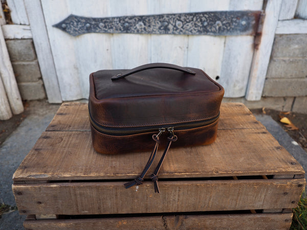 Brown leather dopp kit measuring 9.5 inches long, 6.5 inches wide, and 4 inches tall.  Dark brown leather handle secured to top of bag with copper rivets.  Brass zipper around bag
