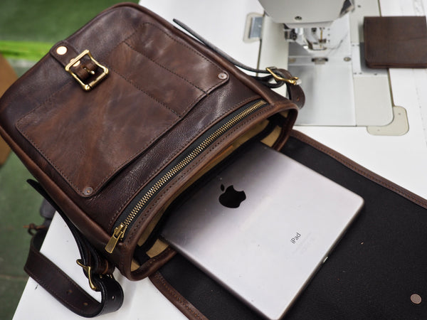 Dark brown leather bag with flap opened.  Front of bag has roller buckle copper riveted to bag.  Antique brass zipper at top and small pocket riveted to bag.  Interior pocket is holding an 12.9 inch iPad Pro