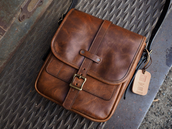 "Brown leather bag with flap measuring 9"" wide, 11"" tall, 3.5"" deep.  Brown leather strap with brass roller buckle securing flap in place."