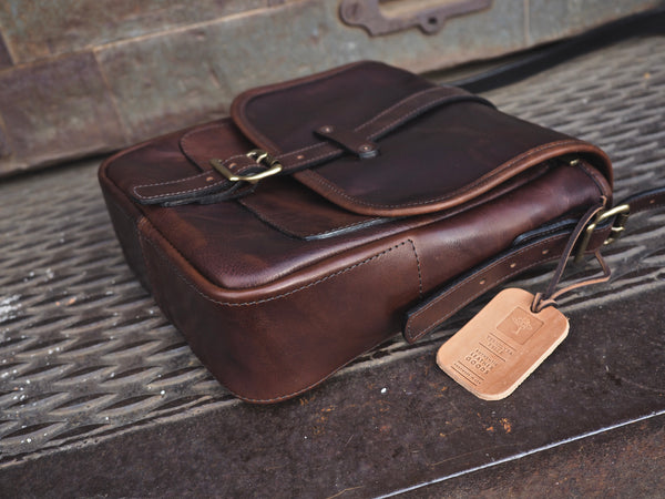"Dark brown leather bag with flap measuring 9"" wide, 11"" tall, 3.5"" deep.  Brown leather strap with brass roller buckle securing flap in place."