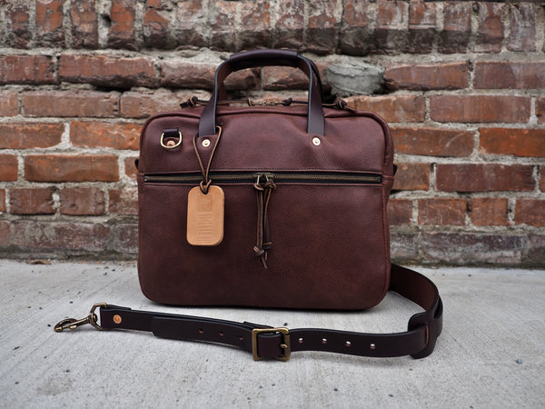 Brown leather briefcase 14 inch width,  11 inches tall, 3.5 inches depth.  Antique brass zipper on front flap.  Leather handles and shoulder strap.