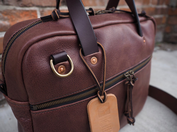 Brown leather briefcase with leather handles and copper rivets.  Brass D-ring to hand shoulder strap to.  Antique brass zipper on front of briefcase.