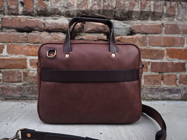 Back of brown leather briefcase with leather handles and shoulder strap.  Brass D-ring and copper rivets secure handle in place.  Brown leather roller bag/trolley frame strap sewed on back.