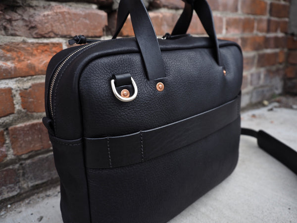 Back of black leather briefcase with leather handles and shoulder strap. Polished nickel D-ring and copper rivets secure handle in place. Black leather roller bag/trolley frame strap sewed on back.