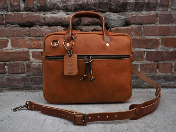 Lighter brown leather briefcase 14 inch width,  11 inches tall, 3.5 inches depth.  Antique brass zipper on front flap.  Leather handles and shoulder strap.