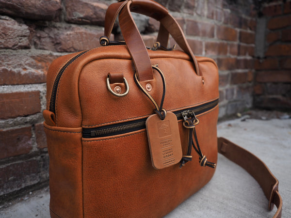 Lighter brown leather briefcase with leather handles and copper rivets.  Brass D-ring to hand shoulder strap to.  Antique brass zipper on front of briefcase.