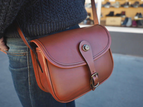 Brown leather purse with flap and leather binding.  Solid brass quick snap and rounded buckle.