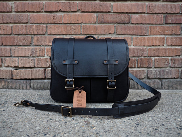 Black selvedge bag measuring 14 inches wide, 11 inches tall, and 3.5 inches depth.  Black leather flap secured to black selvedge bag with two black leather straps and antique brass square roller buckles.  Black leather shoulder strap with antique brass roller buckle and swivel snaps.