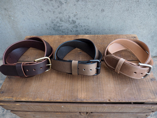 Brown leather 1.5 inch belt with brass rounded buckle.  Grey leather  1.5 inch belt with black stainless roller buckle.  Light brown leather 1.5 inch with white bordering stitch and matte nickel rounded buckle.