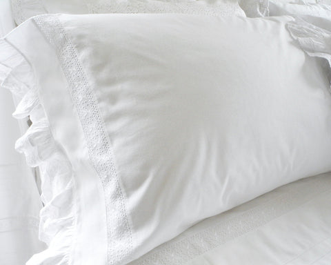 Cotton pillow case is decorated with lace inset and ruffle on the end.