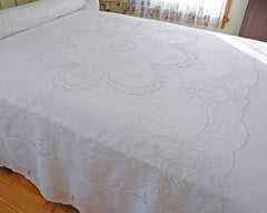 Pure linen bedcover featuring ornate central motif created with cutwork embroidery. Graceful garland like pattern frames the center and all edges, providing for high quality finish. Made by hand on fine quality of 100% linen.
