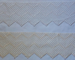 "Exquisite lace trim with classic mosaic like pattern. White or rich cream color. Just under 7"" wide."