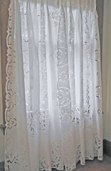 Linen window panels, richly decorated with hand embroidery and finished with pleats at top. All white.