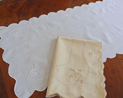 Hand embroidered table runner or dresser scarf. Hand embroidered with scalloped edge and floral motifs.