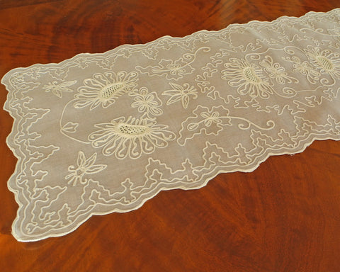 Table runner or dresser scarf embroidered with sunflower like motif and graceful chain stitch along the scalloped edges on 100% cotton organdy. Color is ecru on ecru.