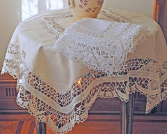 Pure linen tablecloth decorated with hand made cluny lace border and center inset. In white and ecru.