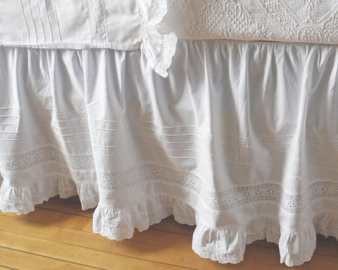 100% cotton dust skirt decorated with several rows of tucks, lace inset and ruffle on the bottom edge.
