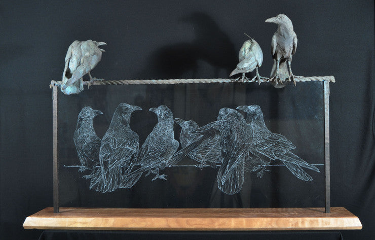 bronze sculptures of ravens atop a glass etching of ravens