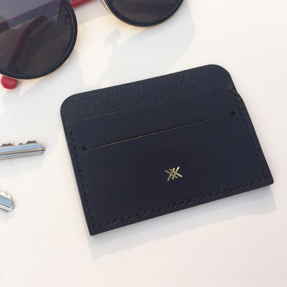 Card holder on a flat surface next to glasses