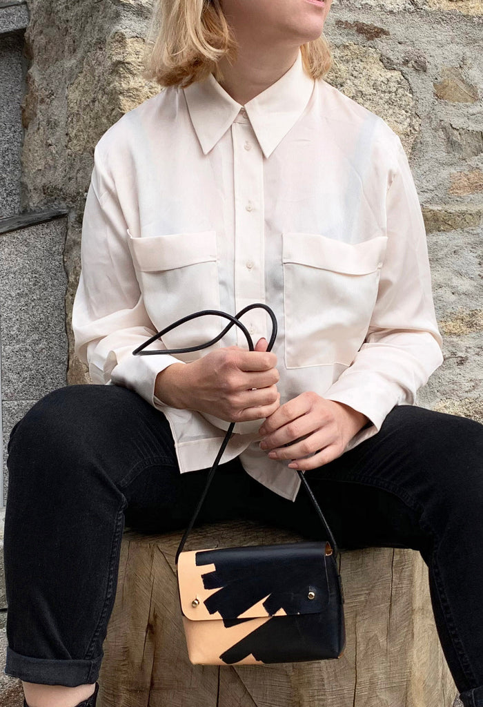 Model wearing a minimalist outfit holding the bag by its strap
