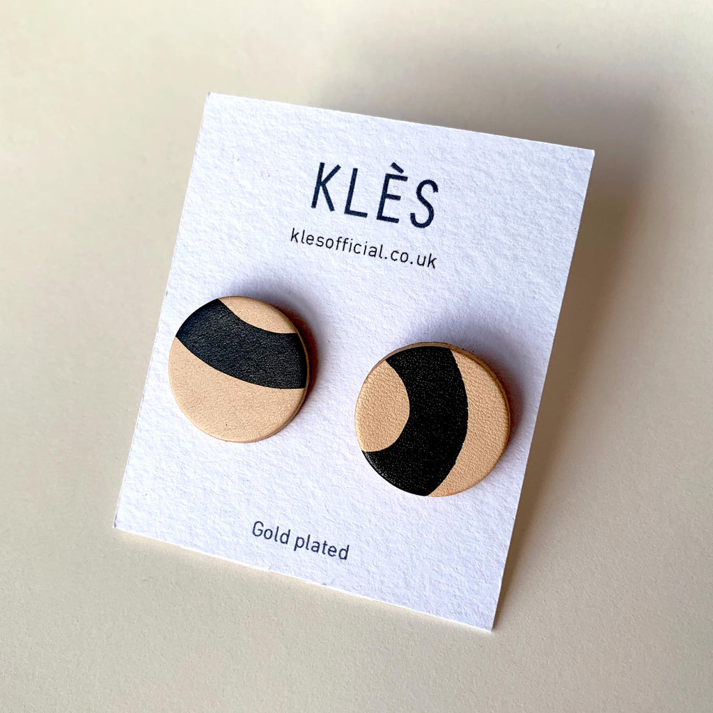 Handmade leather stud earrings on a plain background