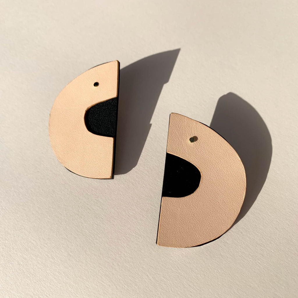 Leather earrings on a natural beige background