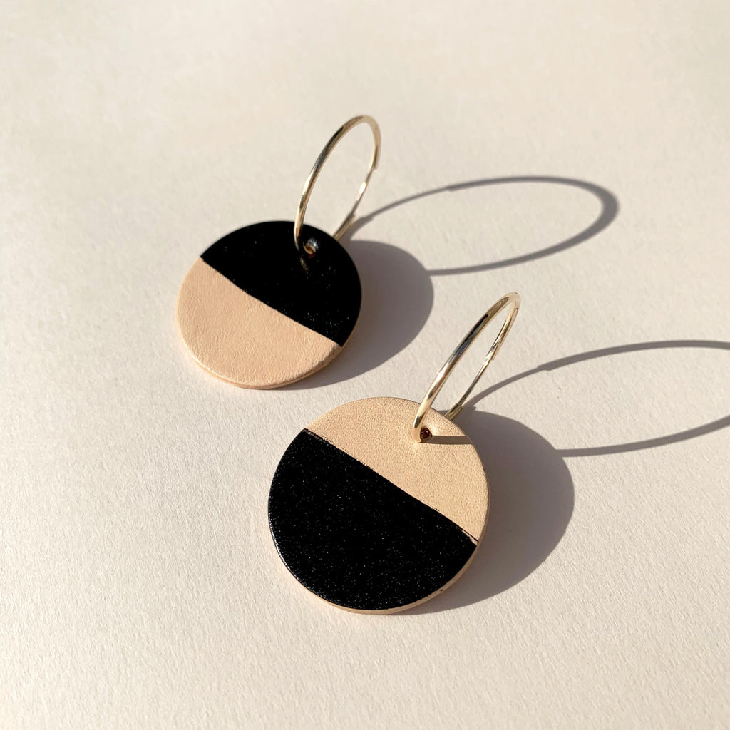 Leather earrings on a soft plain background