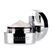 Load image into Gallery viewer, ANJALI MD Yeux Ultimes, Ultimate Eye Wrinkle Repair. An all chrome jar with the cap off and light tan cream inside peaking over the top of the jar.