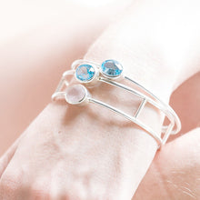 Load image into Gallery viewer, Hand model wearing silver bangle with natural gemstones - sky blue topaz and rose quartz