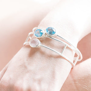 Hand model wearing silver bangle with natural gemstones - sky blue topaz and rose quartz