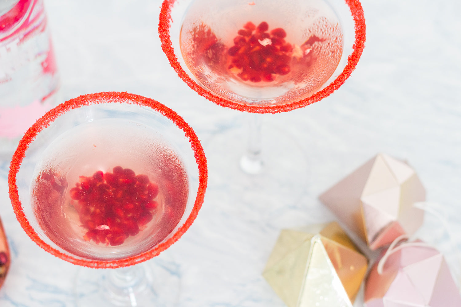 Raspberry cosmopolitan garnish with red decorating sandy sugar