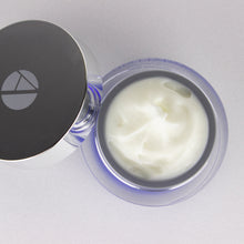 ANJALI MD Brightening Retinol Night Cream - View of Cream swirl in the glass jar from above. The chrome cap to the left side, leans on the glass jar with an A logo on the top.
